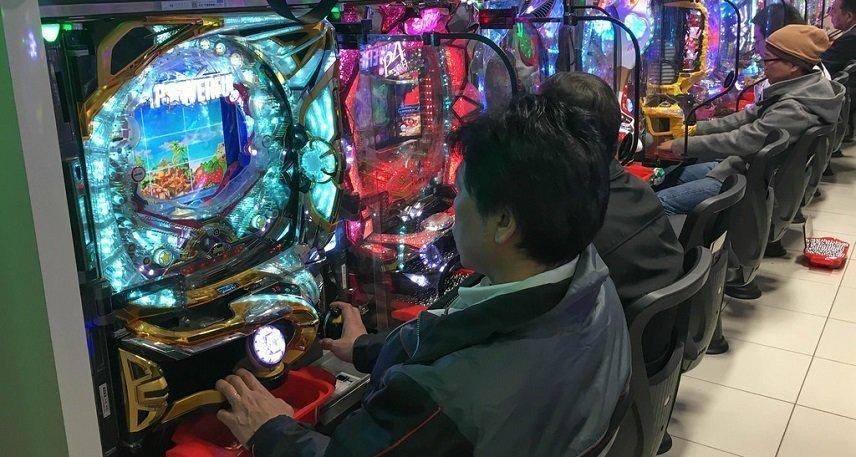 Japaner sitter på rad och spelar japanskt spel.