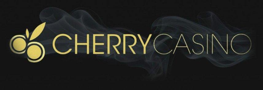 På en svart bakgrund syns texten Cherry Casino i gult och grått. Framför namnet syns två guldfärgade körsbär. Bakomtexten syns en rökeffekt.
