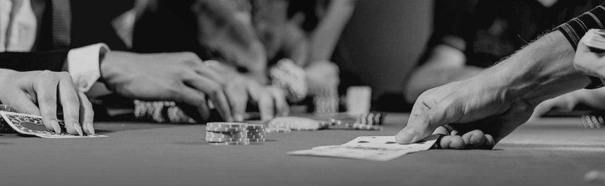 Svartvitt fotografi av ett spelbord. Vi ser ett antal människors händer som delar ut kort och spelmarker.