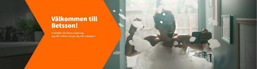 På denna bilden ser vi en kvinna som troligtvis sitter i ett badkar, hon är täckt av badskum upp till axlarna och håller i en mobiltelefon. Hon ser ut att fira någonting. Till vänster om kvinnan syns orange grafik där det är reklam för Betssons välkomsterbjudande.