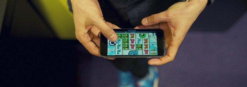 En man spelar casinospel på sin mobiltelefon