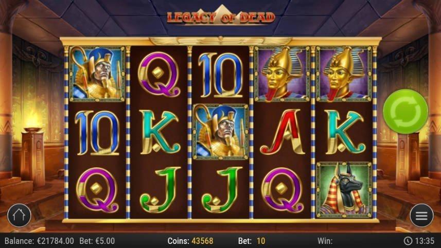På bilden ser vi Play N GO:s online slot Legacy of Dead. I center är spelytan med symboler bestående av bokstäver och faraoner. I bakgrunden syns en gammal gravkammare.