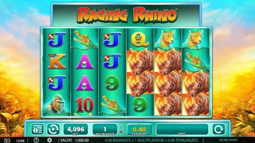 Skärmbild på casinospelet Raging Rhino. Högst upp ser vi spelets logotyp på en turkos bakgrund. Under ser vi själva spelytan med dess symboler, även här är bakgrunden turkos. Symbolerna består av bokstäver, krokodiler, gorillor, leoparder och noshörningar. Nedanför spelytan, med fortsatt turkos bakgrund, ser vi kontrollfältet med meny, autospel, vinstlinjer, multiplikator, insats, vinst och startknapp. Bakom spelautomaten syns gryning i en djungelmiljö.