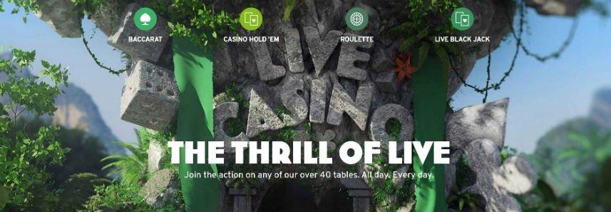 """Bilden visar en djungel där ett stort träd(?) har stenar formade som tärningar hängandes och även stenar som formar ordet Live Casino. Under live casino står det """"The thrill of live. Join the action on any of our over 30 tables. All day. Every day."""" Över ser vi länkar till Baccarat, Casino hold'em, Roulette och Live black jack."""